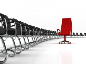 red leader chair with large group of black chairs